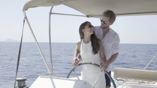 rich young couple steering yacht together slow motion