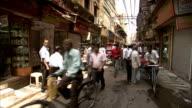 Rickshaws, cyclists and pedestrians crowd a narrow Delhi street.