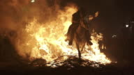 W/S rider and horse crossing a big bonfire