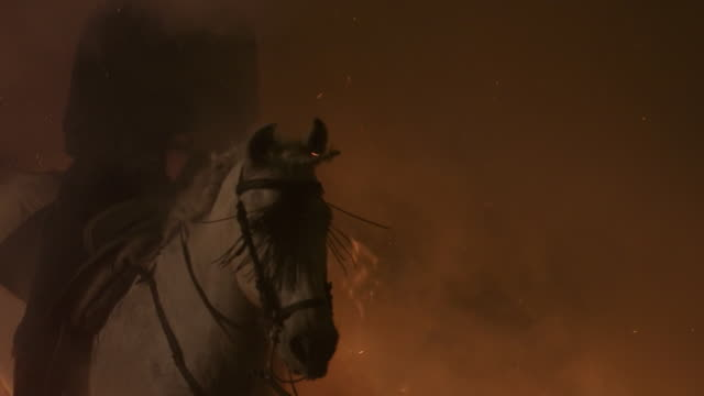 L/S rider and horse jumping over a big flames, smoke