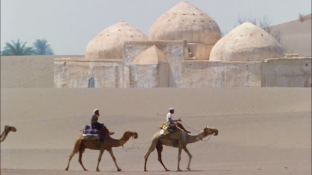 Riders on camels walk by a mosque in Yemen.