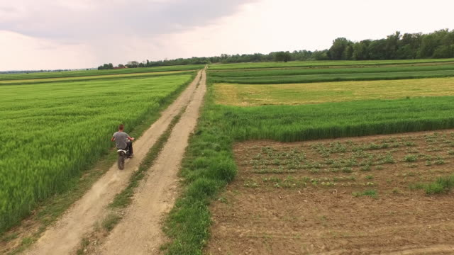 AERIAL Riding a dirt bike along fields