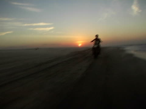 REAR POV, Riding fast on Jericoacoara beach at sunset, Brazil