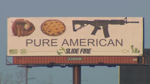 WGN A rifle company has placed a billboard featuring a baseball mitt an apple pie and an assault rifle over the words 'Pure American' raising...