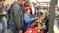 rifle display child browsing weapons Rocky Mountain Gun Show on January 08 2013 in Sandy Utah