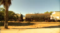WS Driving by railroad w/ tankers parked on tracks chain link fencing around parking area factory or government station BG possibly power