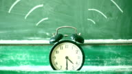 Ringing alarm clock, green blackboard