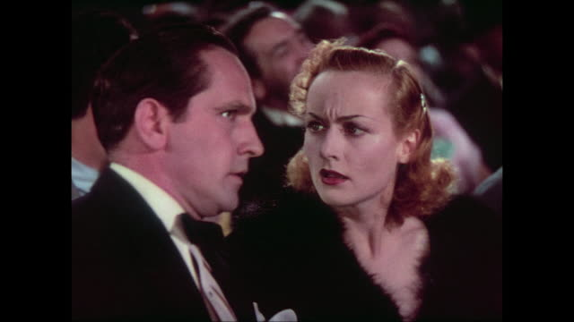 Ringside, dressed in evening wear, man (Fredric March) explains fake wrestling to surprised woman (Carole Lombard)