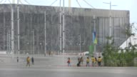 Rio de Janeiro Barra Olympic venues beyond fences / people along in Olympic Park / volunteers along / golf buggy along / tents / fence / cleaners /...