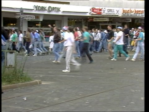 Riots follow England defeat ITN W GERMANY Dusseldorf EXT GV Crowd of fans along RL as shops in b/g BV England fans stand waving arms in air as 'sing'...