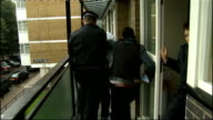 Suspects appear in court Back view arrested suspect taken from flat by police