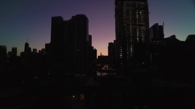 Rising shot of Chicago at sunrise with purple and orange sky