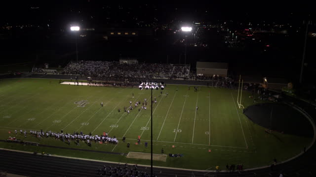Rising view of high school football game at night