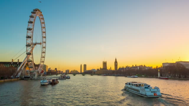 River cruise boat on River Thames and London skyline at sunset.