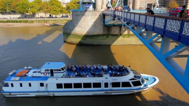 River cruise boat passing under Tower Bridge .