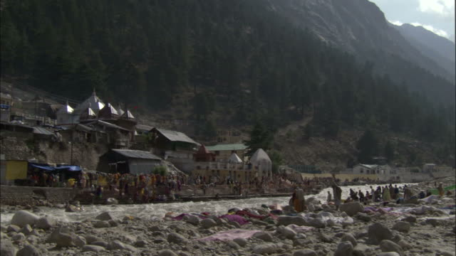 River flows in front of pilgrims by temple, Gangotri, India Available in HD.