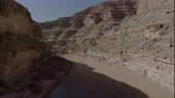A river flows past high canyon walls. Available in HD.
