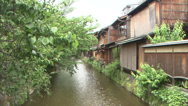 A river flows past wooden buildings on a riverbank.