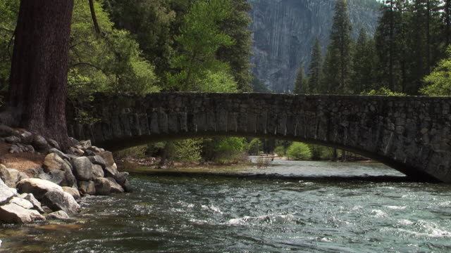 A river flows under a stone bridge. Available in HD.