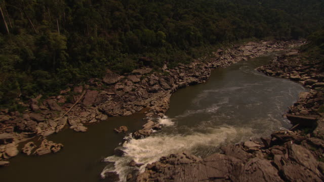 A river snakes past boulders and forested mountains.