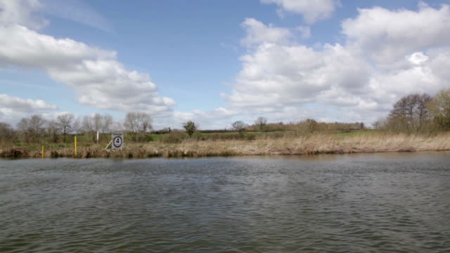 River Waveney Norfolk Broads England flat peaceful big blue sky in spring view from moving boat