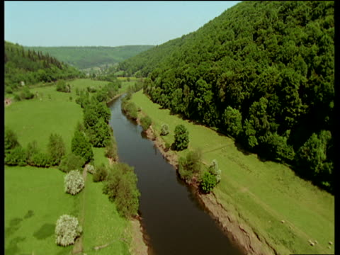 River Wye surrounded by lush green fields and vast forests of the Wye valley.