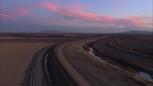 LOW AERIAL Road along US-Mexican border at El Paso at dusk, Texas, USA