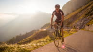 Road cycling on a mountain pass at sunset