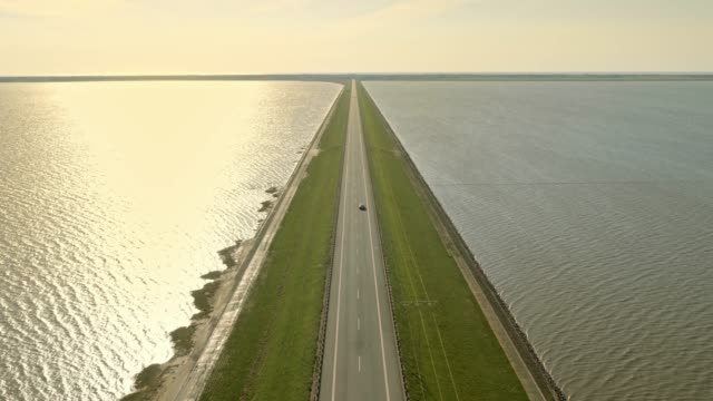 AERIAL Road on a dam in sunshine