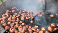 Roast Chinese chestnuts in big pan , Beijing , China.