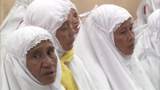 Robed  Islam women sit and whisper prayers.
