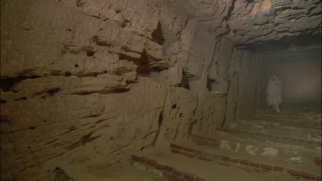 A robed woman walks slowly through catacombs in Cairo.