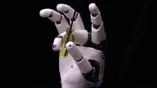 A robot hand manipulates tools.