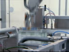 Robotic arm lifting packaged pharmaceuticals off assembly line and placing in box