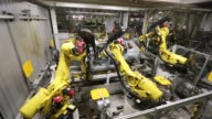 Robotic arms and employees work on the shells of automobiles on the production line at the Volkswagen Group Rus OOO plant in Kaluga Russia on Tuesday...