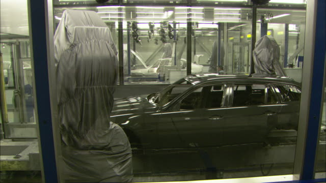 Robotic arms open the doors and the trunk of a car shell on an assembly line in an automobile factory.