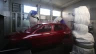 Robotic arms spray the body shell of a VW Tiguan automobile red in the paint shop at the Volkswagen Group Rus OOO plant in Kaluga Russia on Tuesday...