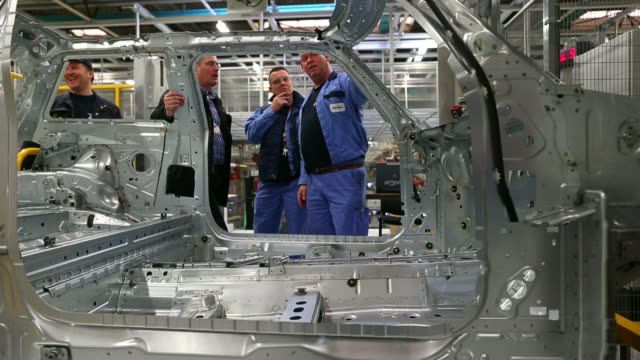 Robotic arms stand beside the chassis of a Mini Hatch automobile produced by Bayerische Motoren Werke AG during testing at the VDL Nedcar factory...