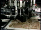 Robotic machine stamping electronic components into computer microchip circuit board