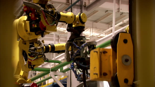 Robots assemble cars on an assembly line in a car factory. Available in HD