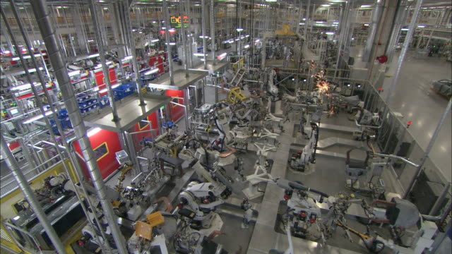 Robots weld and assemble in an automotive factory.