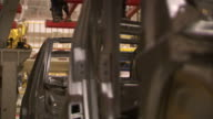 Robots work on a chassis in a car factory. Available in HD