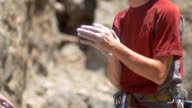 A rock climber putting chalk on his hands for better grip. - Slow Motion