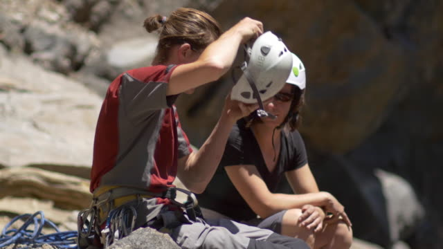 Rock climbers using their helmets.