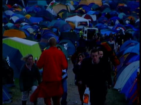 8 crushed to death LIB Glastonbury People to and fro along path at festival TILT UP massed crowds watching performer on stage