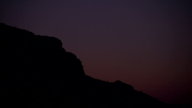 A rock formation silouetted against a purple sky Available in HD.