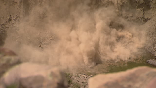 Rocks and dirt fall over a cliff and tumble into water, leaving columns of dust behind.