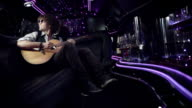 Rockstar in limousine jams on acoustic guitar for fans and paparazzi at awards show