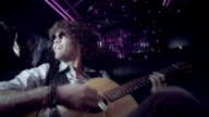 Rockstar jams on acoustic guitar in limousine, fans watch through the windows at awards show
