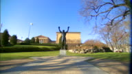 Rocky statue blue sky green grass hedges trees bare tree branches FG Museum of Art BG Sports boxing triumph victory underdog pop culture iconic...